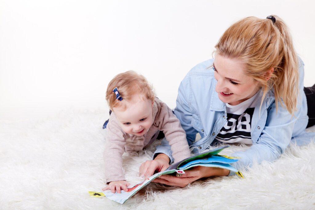 Na zdjęciu widać mamę z dzieckiem, które leżą ma białym, długowłosym dywanie. Kobieta ma blond włosy spięte w kucyk. Ubrana jest w białą koszulkę oraz niebieską koszulę. Kobieta jest uśmiechnięta. Przegląda z dzieckiem książkę. Dziecko ma we włosach granatową spinkę.
