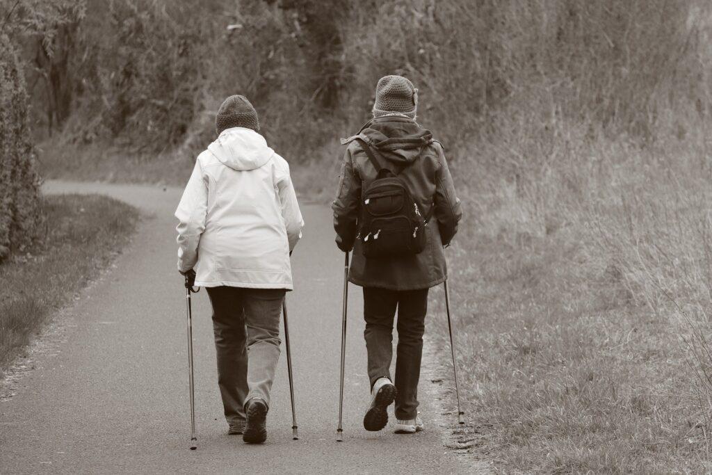 Zdjęcie jest w sepii. Widać na nim dwie starsze kobiety uprawiające nordic-walking. Kobiety są tyłem idą polna drogą. jedna z kobiet ma plecak. Ubrane są w czapki i kurtki.