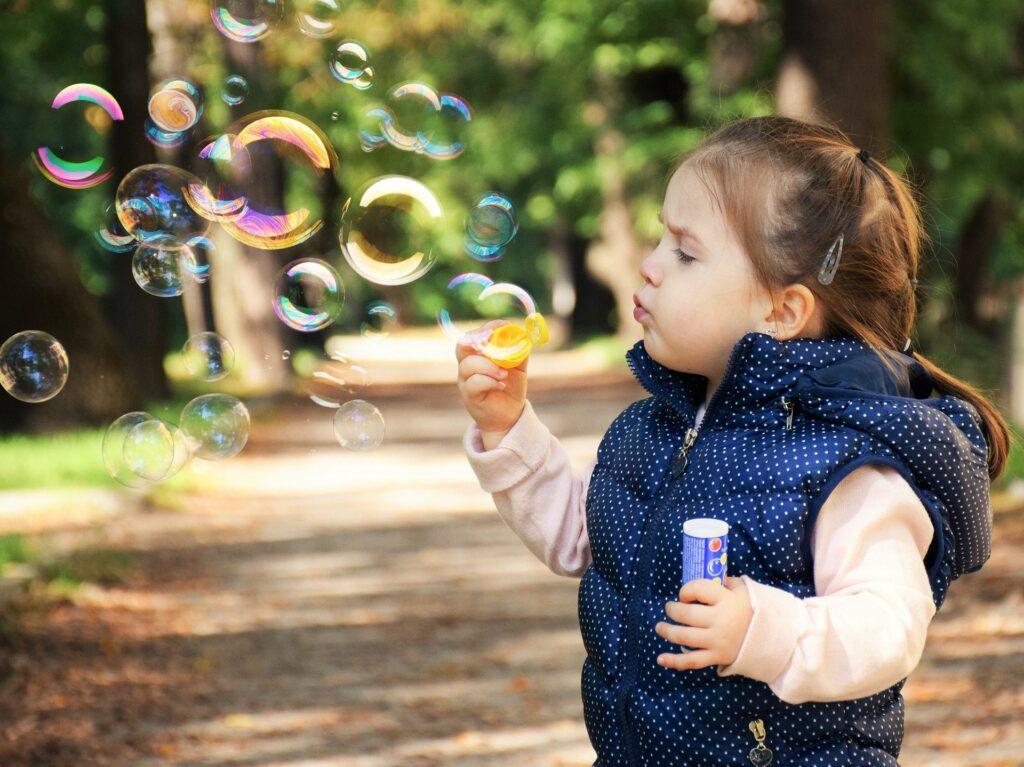 Na zdjęciu widać małą dziewczynkę, która puszcza mydlane bańki. Ma brązowe włosy, spięte w kucyk. Ubrana jest w różową bluzę oraz granatowy bezrękawnik w białe kropki.