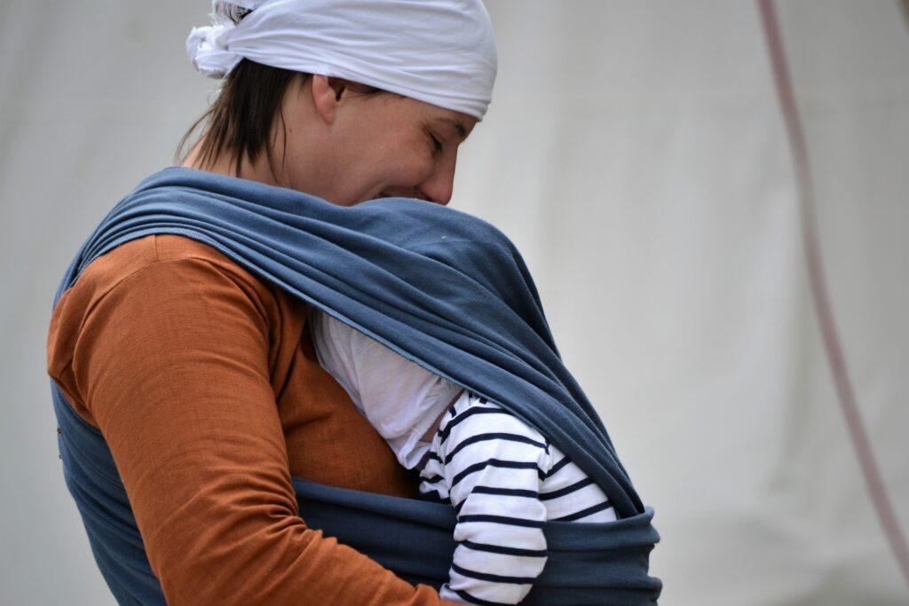 Na zdjęciu widać mame z dzieckiem trzyma dziecko w zawiniętej granatowej huście przy piersi. Na głowie ma biała chustę ubrana jest w pomarańczową koszulkę z długim rękawem. Dziecko ubrane jest w koszulke w biało-czarne paski. Nie widać twarzy dziecka. Są na białym tle.