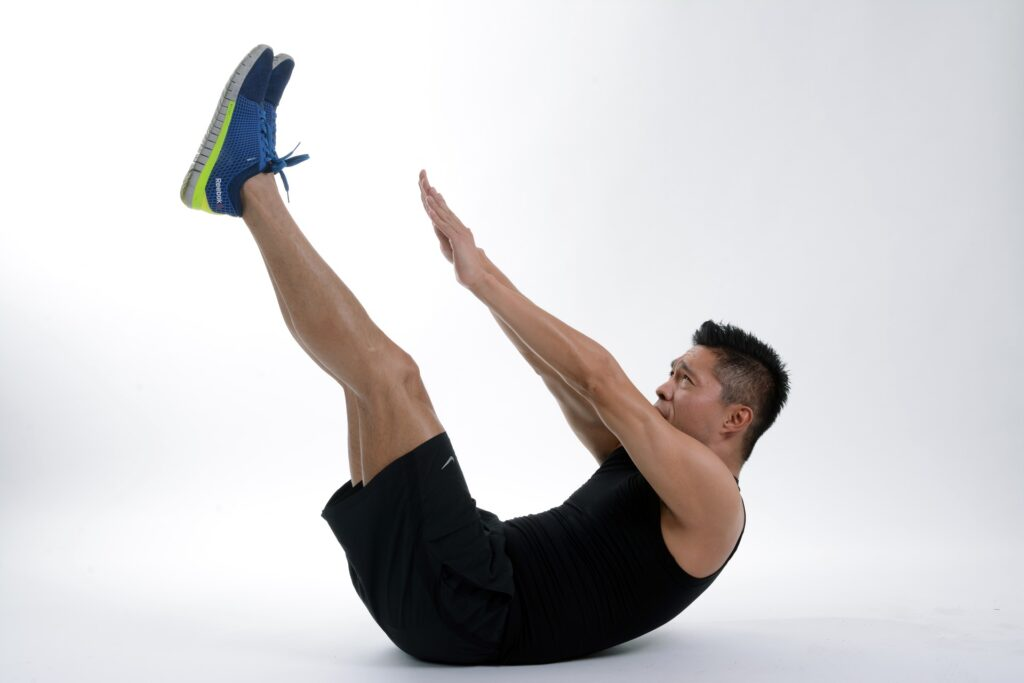 Na obrazku widać mężczyznę w czarnych włosach, ubranego w czarny strój sportowy. Mężczyzna jest w czasie wykonywania ćwiczenia na mięsnie brzucha. Jest w pozycji leżącej i łączy stopy z dłońmi na wysokości brzucha. Ma granatowe buty i jest na białym tle.