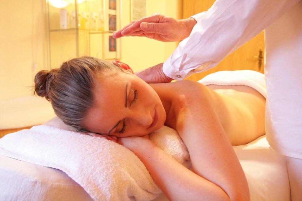 Na zdjęciu widac kobiete która jest w czasie masażu pleców. Lezy na stole do masażu, ma zamknięte oczy i wygląda na zrelaksowana. Po prawej stronie obrazka widać fragment masażysty który dotyka jej pleców.