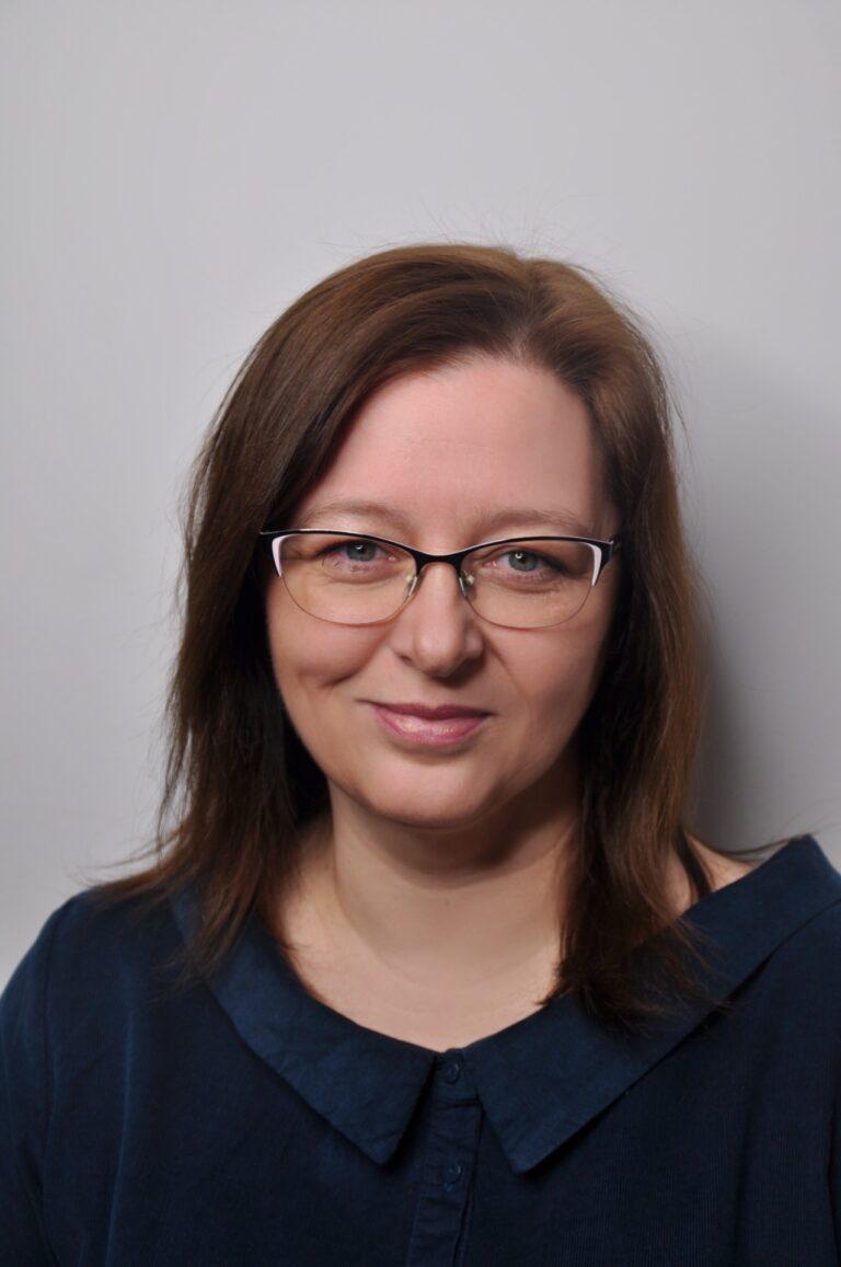 Zdjęcie przedstawia portret Pani Agnieszki Stemblewskiej na szarym tle. Ma ona okulary i brązowe włosy do ramion. Ubrana jest w granatowa koszulę z kołnierzem.