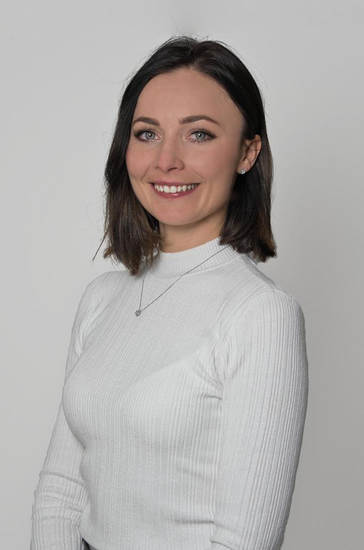 Na zdjęciu na szarym tle jest uśmiechnięta Pani Natalia Danek w białym półgolfie. Ma krótkie ciemne włosy.